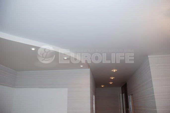 Матовый натяжной потолок, переходящий единым полотном из центрального помещения в узкий коридор.