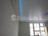 Двухуровневый натяжной потолок в комнате с применением скрытой светодиодной подсветки за верхним полотном