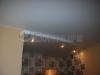 Простой двухуровневый потолок в квартире-студии. Потолок таким образом разделяет помещение на зоны кухни и центрального помещения.
