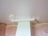 Сатиновый натяжной потолок. На поверхности потолка видны характерные блики.