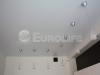 Матовый белый натяжной потолок ПВХ с подвесными светильниками.