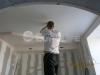 Матовый натяжной потолок ПВХ в процессе монтажа осветительного прибора.