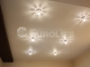 Матовый белый натяжной потолок со встроенными светильниками.