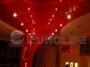 Простой глянцевый потолок с так называемыми «натяжными люстрами». Отраженные лампы в натяжной потолке дают необычный эффект.