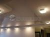 Сложный комбинированный многоуровневый потолок. Нижние плоскости и борта смонтированы из тканевого полотна, верхние части из глянцевого белого потолка ПВХ со светодиодной подсветкой.