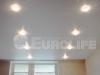 Матовый белый потолок в спальне с двумя рядами встраиваемых светильников.
