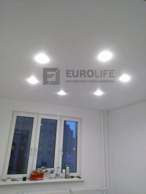 Матовый белый потолок со светильниками кругом