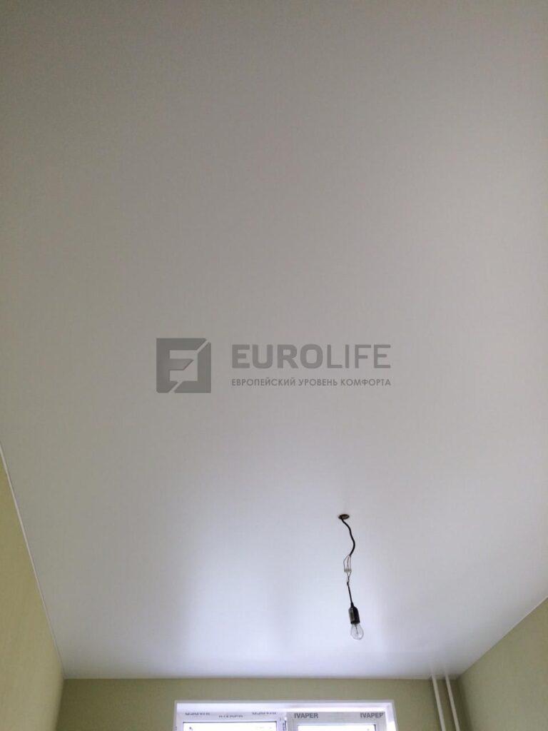 Белый матовый потолок с 1 люстрой и обводом двух труб