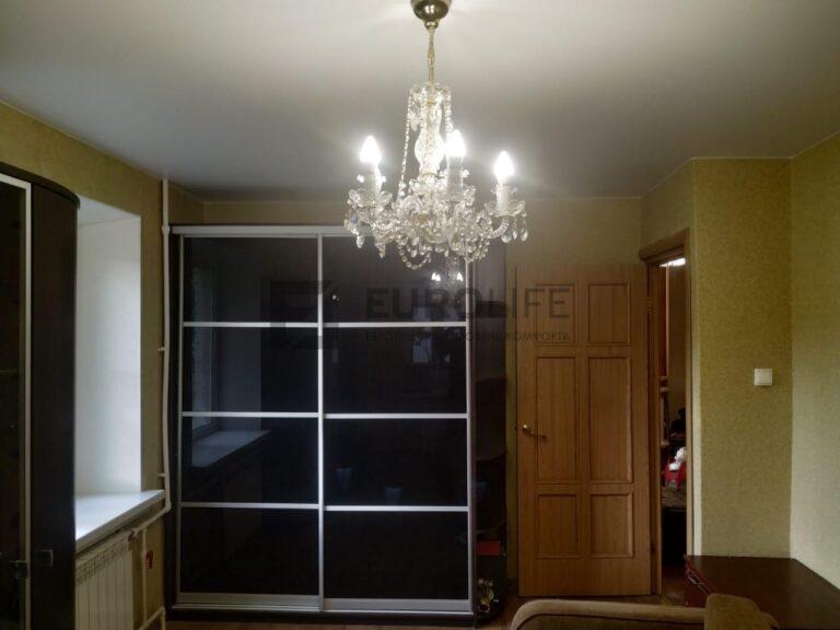 натяжной потолок в стандартной комнате с 6 углами, 1 люстрой и 1 трубой