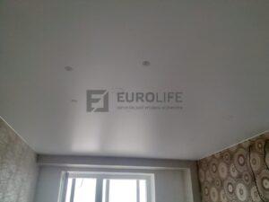 Сатиновый потолок подготовлен к установке освещения. Кольца и крепежи выставлены под люстру-паука и светильники