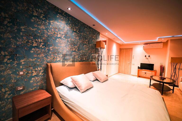 белый матовый двухуровневый потолок с закарнизной подсветкой в спальне