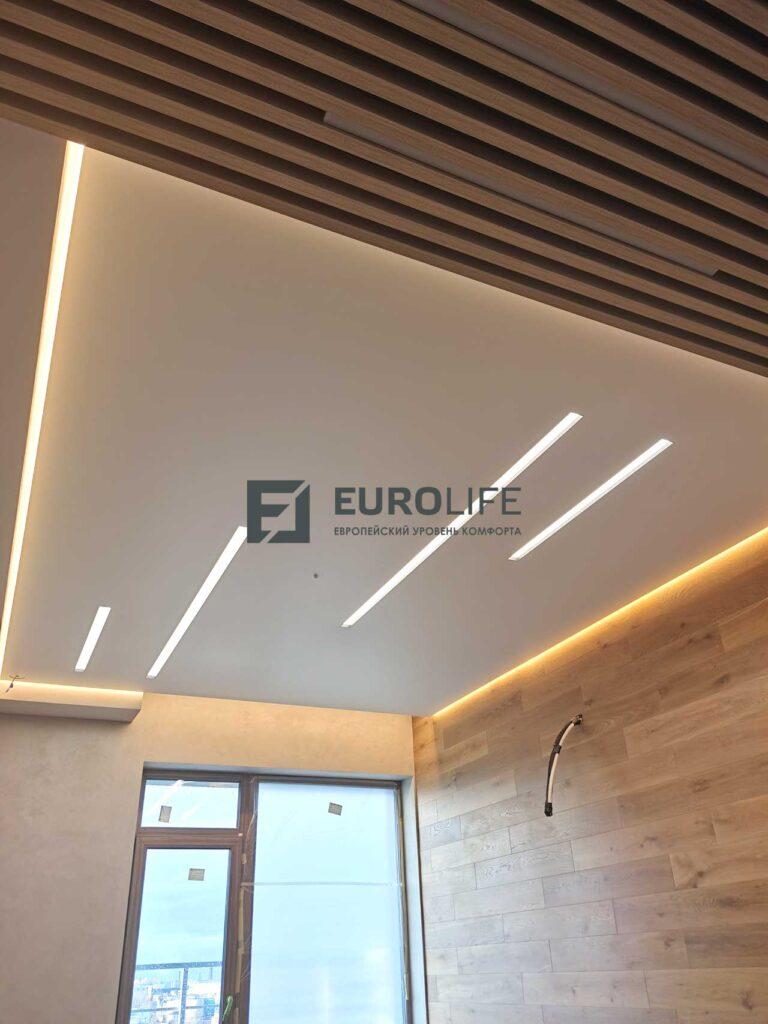 белый матовый парящий потолок со световыми линиями SLOTT и скрытым карнизом в гостиной