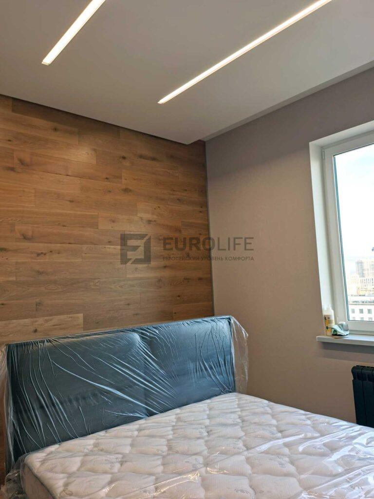 белый матовый парящий потолок со световыми линиями SLOTT и скрытым карнизом в спальне