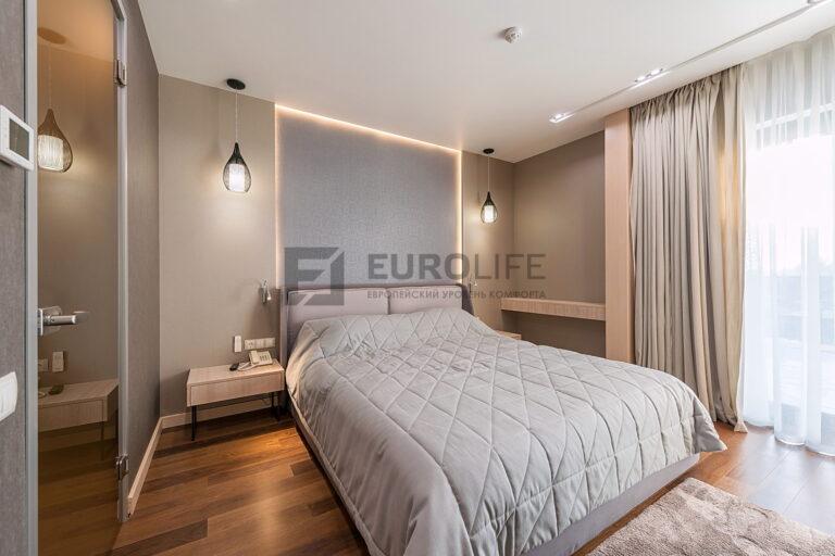 белый сатиновый потолок со скрытым карнизом, нишей SLOTT под светильники и парящей подсветкой прикроватной зоны в спальне