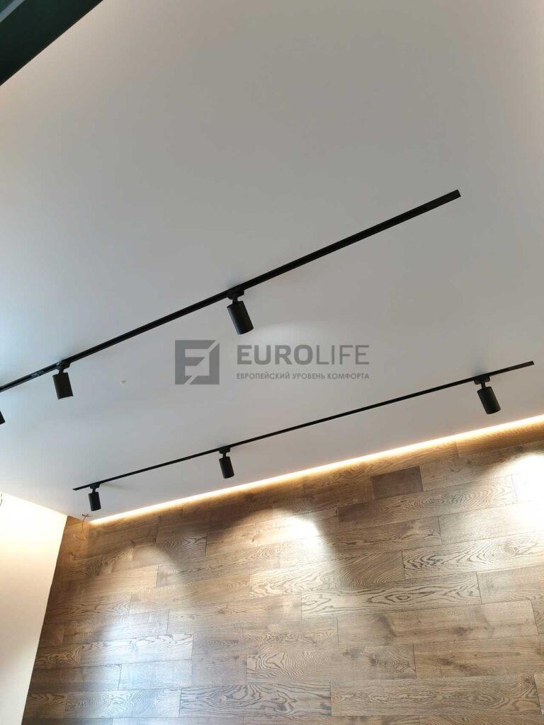 белый матовый парящий потолок со скрытым карнизом и встроенными трековыми светильниками в детской