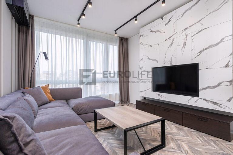 белый матовый потолок со скрытым карнизом и трековыми светильниками в гостиной