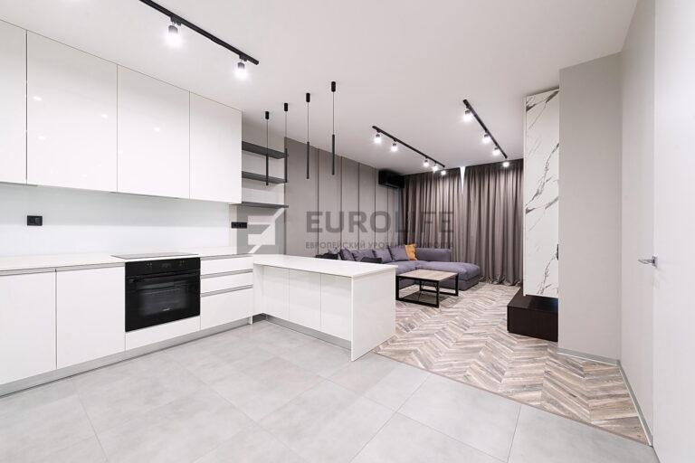 белый матовый потолок со скрытым карнизом и трековыми светильниками в квартире студии