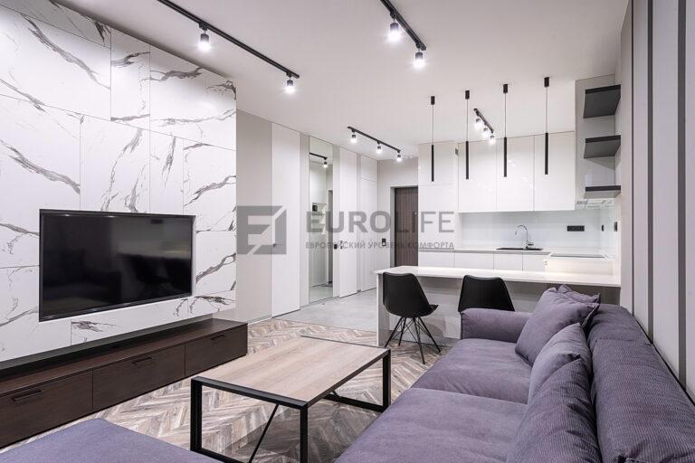 белый матовый потолок в квартире студии с трековыми светильниками и подвесами