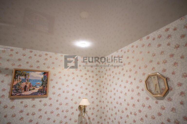 белый потолок, в котором отражается цвет обоев и пола