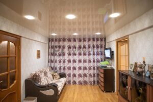 глянцевый потолок в гостиной со скрытой нишей для штор