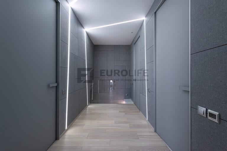 светлый матовый потолок со световыми линиями переходящими на стены в коридоре
