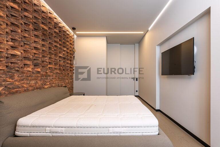 светлый сатиновый парящий потолок со световой линией и подвесами в спальне
