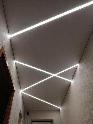 В коридоре перекрестия световых линий позволяют оживить и расширить узкое пространство.
