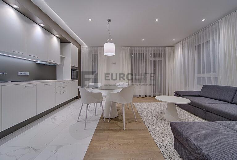 белый матовый потолок с подсвеченной нишей в совмещенной кухне гостиной