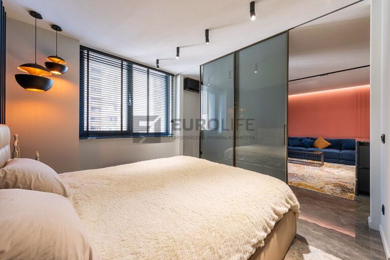 белый потолок с нишей под перегородку в спальне с контрастными черными светильниками