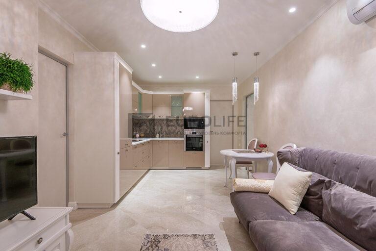 белый матовый потолок с точечными светильниками подвесами и люстрой в совмещенной кухне