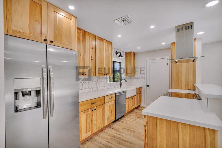 белый сатиновый потолок с отверстием под вентиляцию и обводом вытяжки над островом на кухне