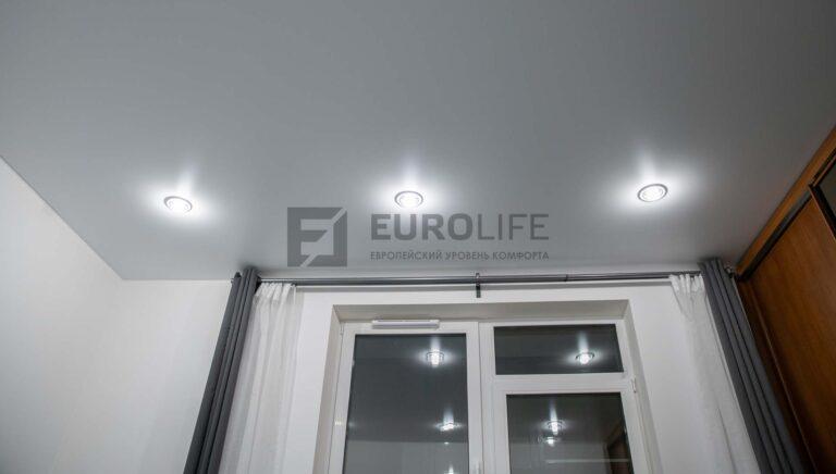 сатиновый потолок в гостиной со светильниками