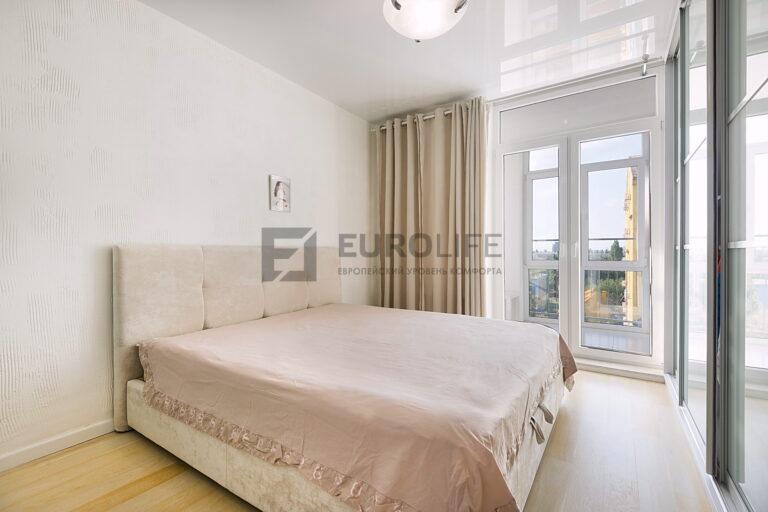 глянцевый натяжной потолок в спальне с интеграцией шкафа купе