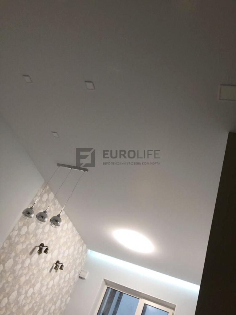 белый тканевый натяжной потолок со скрытым карнизом с подсветкой в гостиной